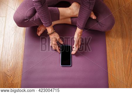A Girl Practicing Yoga And Meditation At Home On A Lilac Carpet Using A Smartphone And A Mobile App.