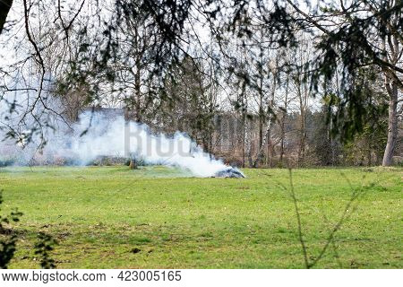 Burning Pile Of Dry Branches With Big Smoke In Green Field Outside, Burns Green Wasted Farming Conce