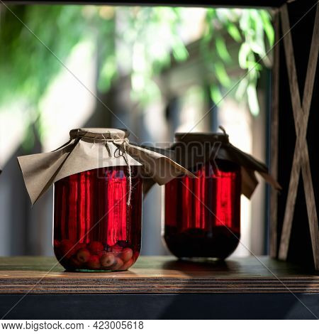 Red Berry Compote In Glass Jars. Two Cans Of Preserved Or Canned Cherry Drink On Wooden Table In Fro
