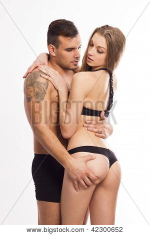 Sexy passionate young couple hugging on white isolated background