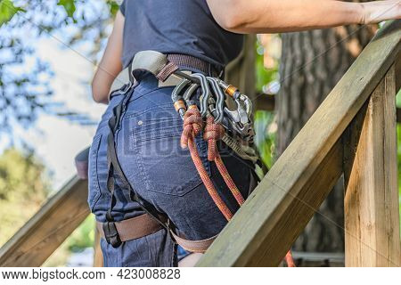 Forest Adventure Park. The Woman Fastens Her Carabiner And Uses The Climbing Equipment. Overcome Obs