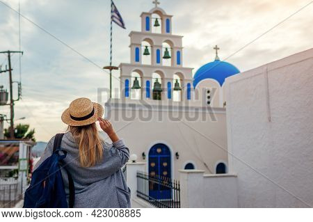 Santorini Tourist With Backpack Walking By Church In Akrotiri On Santorini. Woman Enjoys Architectur