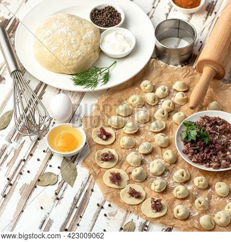 Dumplings Cooking Process. Minced Raw Meat Filling On Raw Dough Circles At Rustic Table. Ingredients