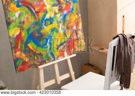 Oil painting and wooden chair with apron. Art still life and paintbrush painting in artist creative studio interior with painter tool