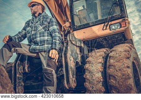 Excavation Construction Works. Caucasian Excavator Operator In His 40s In Front Of His Machine.
