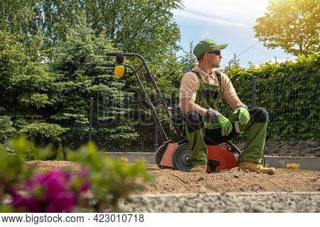 Professional Caucasian Gardener In His 40s Relaxing While Seating On His Gasoline Lawn Aerator After