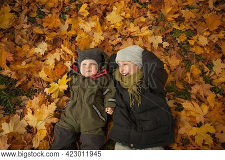 Happy Brothers Laughing And Lying On Autum Fall Leaves Background. Boy 9 Years Old And Little Baby B