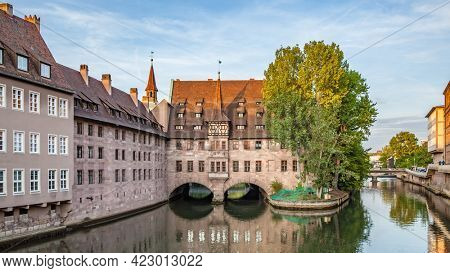 Hospice of the Holy Spirit and Pegnitz river in Nuremberg in the evening, Germany. Panoramic view, german cityscape