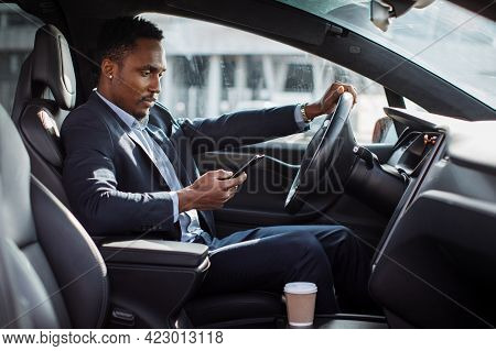 Young African American Man In Business Suit Driving Car And Using Modern Smartphone. Busy Multitaski