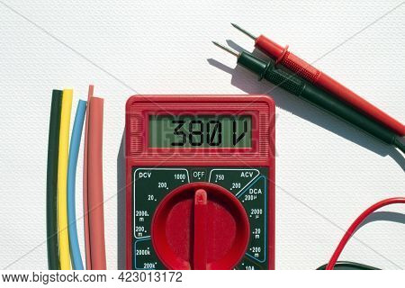 Multimeter With Text On Display 380 V And Heat Shrink Insulation On White Background. Construction A