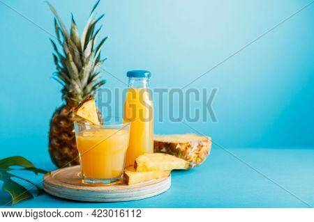 Tasty Pineapple Juice In Glass With Ingredients, Glass Juice Bottle On Blue Color Summer Background.