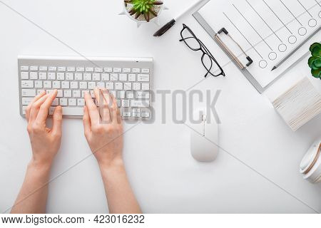 Female Hands Typing On Keyboard At White Table Workplace. Home Office Workspace With Keyboard Mouse