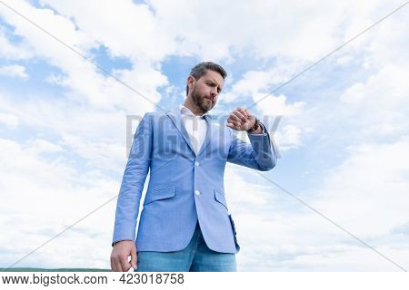 Handsome Mature Man Businessman In Formal Suit Check Time On Wristwatch On Sky Background, Time