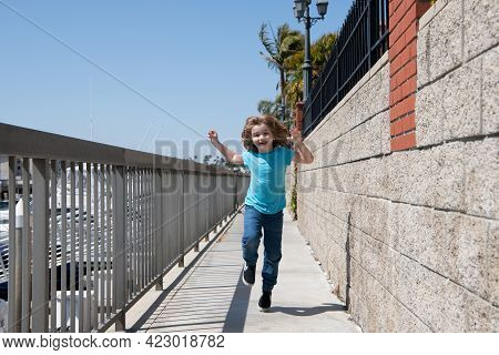Happy Energetic Boy Child Enjoy Free Time Running On Promenade During Summer Vacation, Freedom