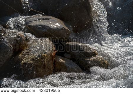 The Chaos Of A Fresh Clear Mountain Creek Flowing Over Sunny Rocks While Splashing Water Drops And C