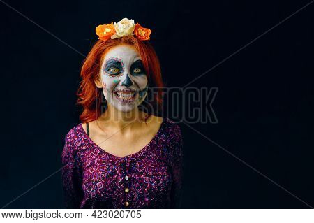 A Young Woman In Day Of The Dead Mask Skull Face Art. Woman With Skull Makeup And Red Hair Showing T