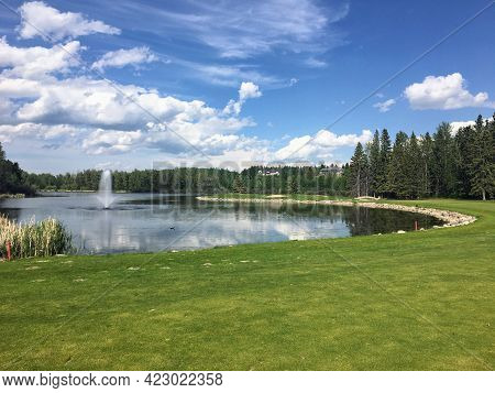 A Beautiful View Of A Par 4 Golf Hole Surrounded By A Giant Lake And A Fountain.the Scenic Hole Requ