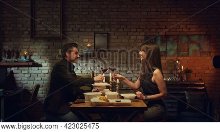 Couple having romantic quarantine dinner at home, eating from takeaway box and drinking red wine. Stay at home and order food online.