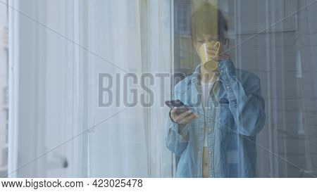 Adult woman standing in window at home daydreaming drinking coffee and checking phone at morning.