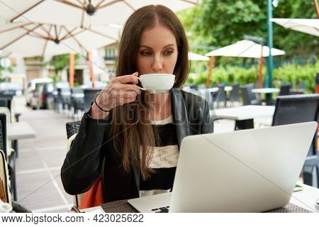 Young adult woman drinking tea and working with laptop computer on restaurant terrace.