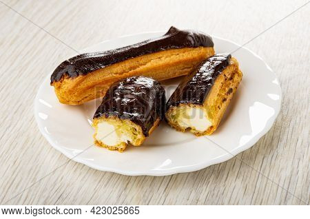 Whole Eclair With Chocolate Glaze, Halves Of Eclair In White Plate On Wooden Table