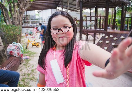 A 6-year-old Girl Reach Out Her Hand Against To Cover The Camera. Shy Child. Children Wears Eyeglass