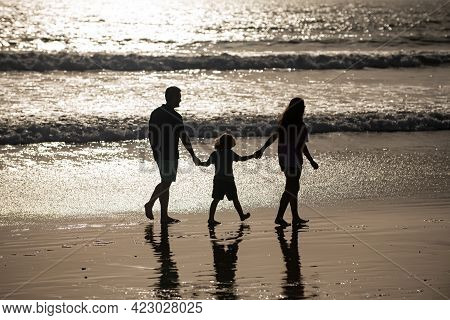 Silhouette Of Father, Mother And Child Son Holding Hands And Walking On Beach. Sctive Fanily Lifesty