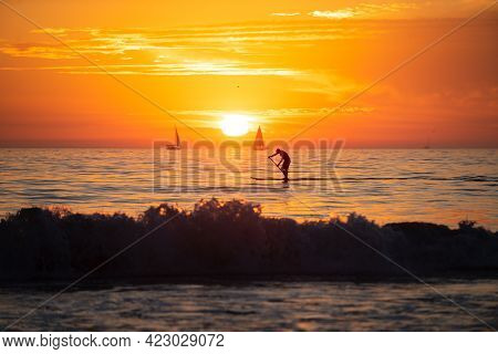 Paddle Boarding During A Beautiful Sunrise. Panoramic View Of Sunset Over Ocean. Beautiful Serene Sc