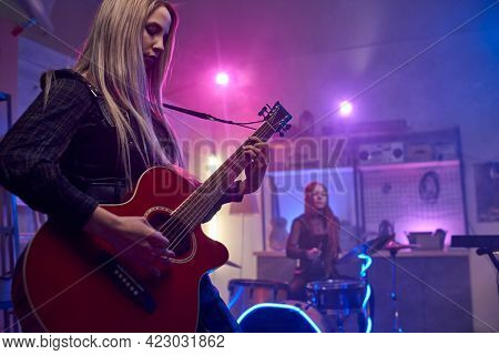 Pretty blond female playing electric guitar during stage performance