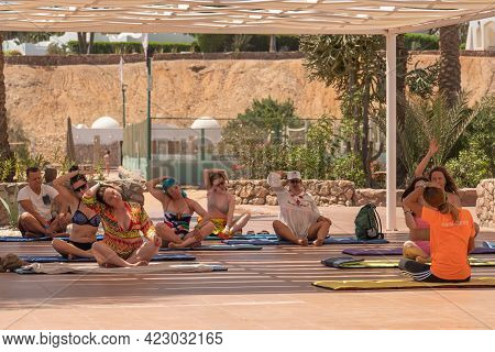 Sharm El Sheikh, Egypt - May 18 2021: Group Of Guests Of The Resort Hotel Doing Yoga Under An Awning