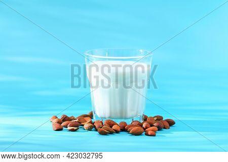 Almond Milk With Almond Kernels. Alternative Milk For Vegetarians. Milk In A Glass On A Blue Backgro