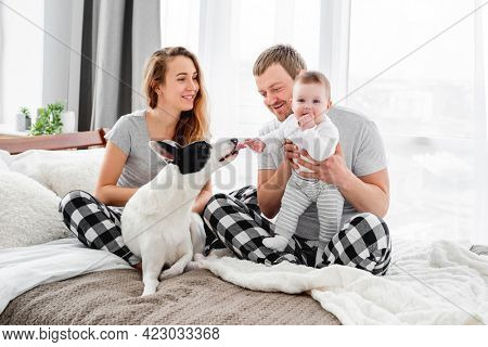 Family with baby boy sitting on the bed with cute dog. Mother and father with their son and doggy together smiling. Beautiful parenthood time. Pet with owners