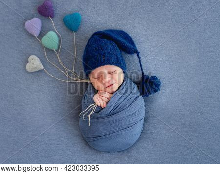 Newborn baby boy swaddled in blue fabric and wearing hat sleeping and holding knitted toy hearts. Photo composition with infant kid napping on blue backgroung