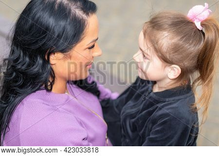 Cute 5 Years Old Girl And Her Mom Sit On A Park Bench In Summer.holding Her Daughter While Sitting O