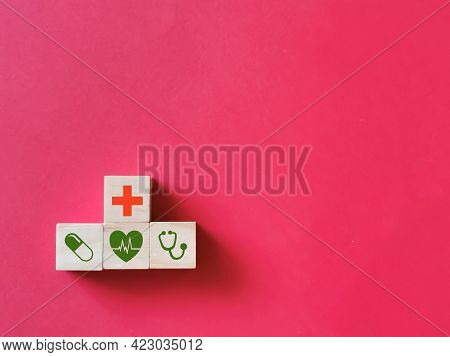 Health Insurance Concept. Wooden Cubes With Health Care Icons Isolated On Red Background.