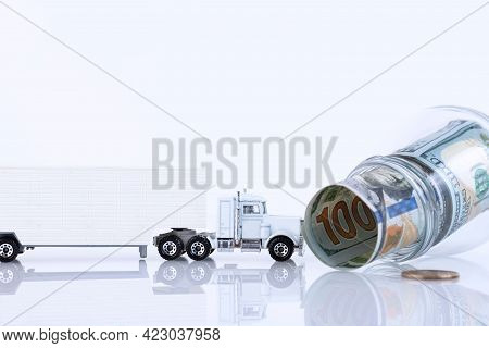 Glass Jar Full Of 100 Dollar Bills Lying Sideways And A Lorry Isolated On White. Copy Space.