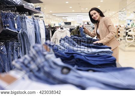 Woman Salesman Laying Out Jeans In Shop Window