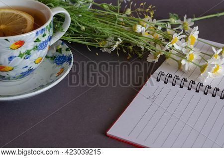 Flowers, A Cup Of Tea, And An Open Blank Notepad On A Gray Background. Small Field Daisies On Top Of