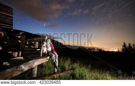 Woman Traveler Hugging Cute Dog While Enjoying Fantastic View Of Night Starry Sky. Female Hiker With