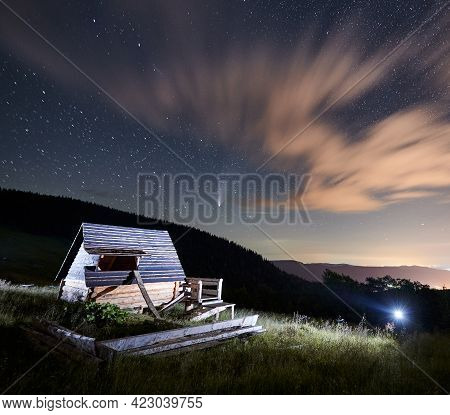 Magnificent View Of Night Starry Sky Over Grassy Hill With Old Wooden House. Beautiful Landscape Of