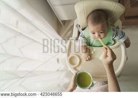 Asian Little Cute Baby Boy Sitting In High Chair Eating First Food From Spoon With His Mother At Hom