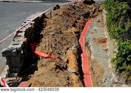 Disassembly Of Interlocking Paving And Laying Of Cable Electricity. Covered With Red Safety Tape. Re