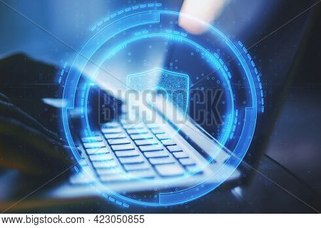 Close Up Of Hands Using Laptop With Abstract Glowing Shield Lock On Blurry Background. Antivirus And