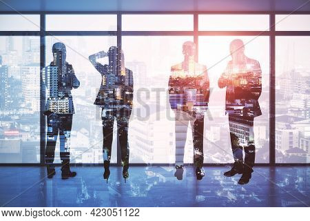 Backlit Businesspeople Standing In Modern Office Interior With City View. Teamwork And Success Conce