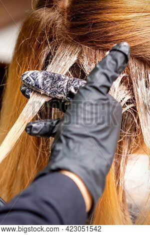 Closeup Back View Of Hairdresser\'s Hands In Gloves Applying Dye To A Strand Of Hair Of Redhead Youn