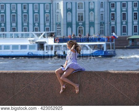 Summer Wind Plays With The Dress Of A Girl Sitting On The Granite Fence Of The River Embankment, Adm