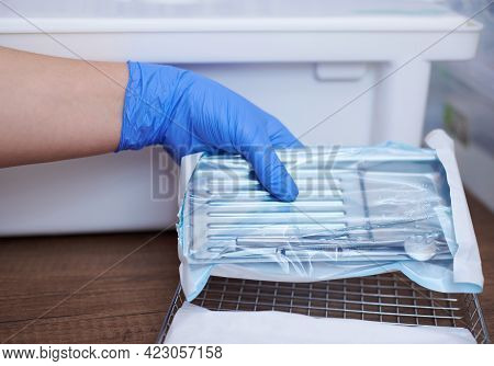 Dentist Loading Steel Dental Instruments Sealed In Separate Airtight Packaging In A Steam Autoclave