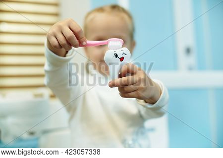 Adorable Child Brushing A White Toy Tooth With A Toothbrush In The Dental Office. Oral Care Concept
