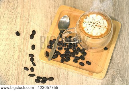 Hot Brewed Coffee With Frothed Milk On A Wooden Tray Lined With Fresh Coffee Beans On The Table The