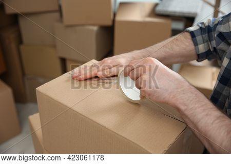 Man Taping Cardboard Box Indoors, Closeup. Moving Day